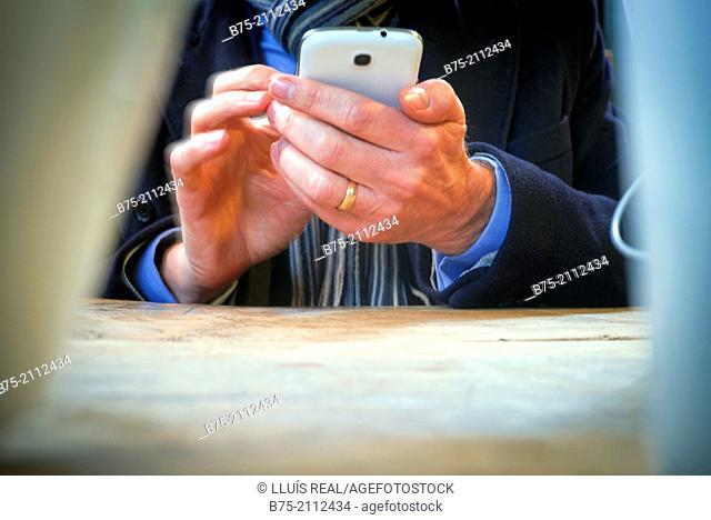 Closeup of the hands of a man unrecognizable manipulating one phone. London, England, UK, Europe