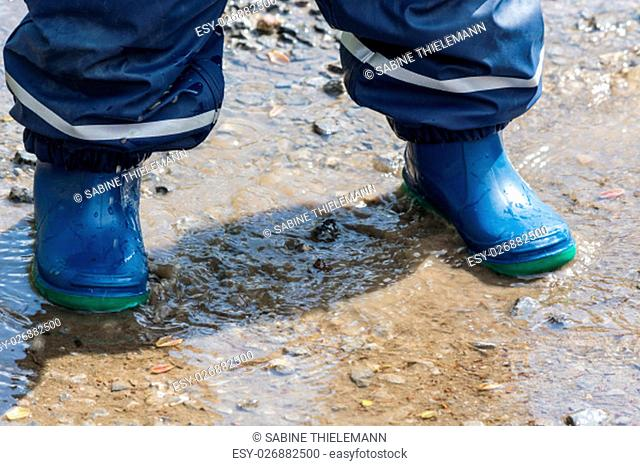 child with blue rubber boots in a puddle. close-up .