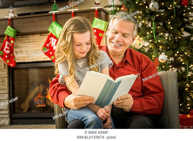 Caucasian grandfather reading to granddaughter at Christmas