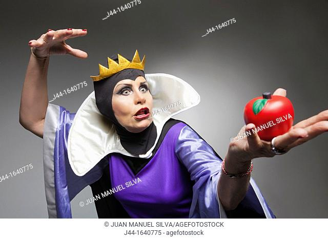 Mature woman wearing the evil queen costume holding a plastic apple