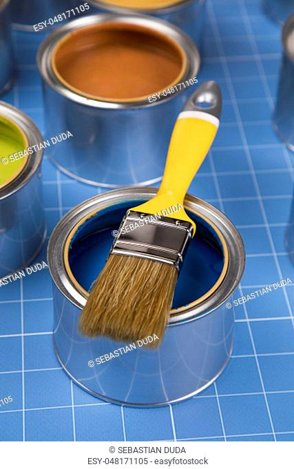 Colorful paint can, brush, blue background
