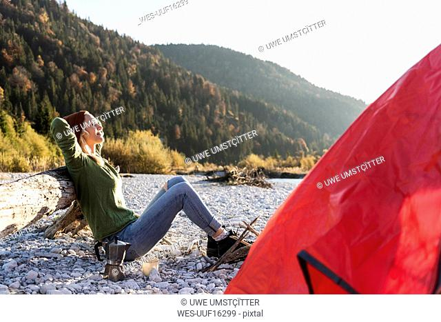 Mature woman camping at riverside in the evening light