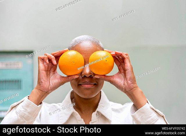 Woman covering her eyes with oranges outdoors