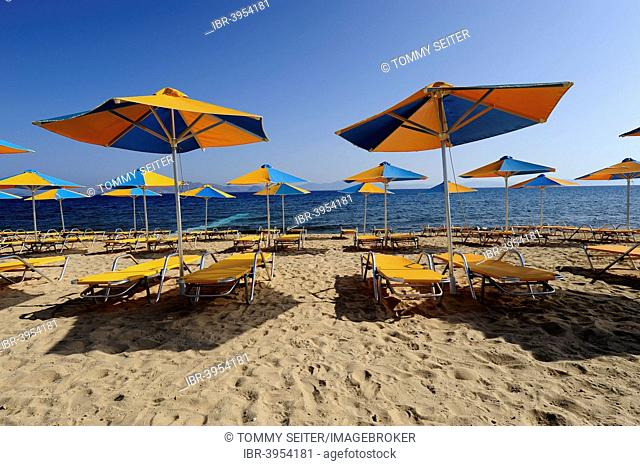 Parasols and sun loungers on the beach in Psalidi, Kos Island, Dodecanese, Greece