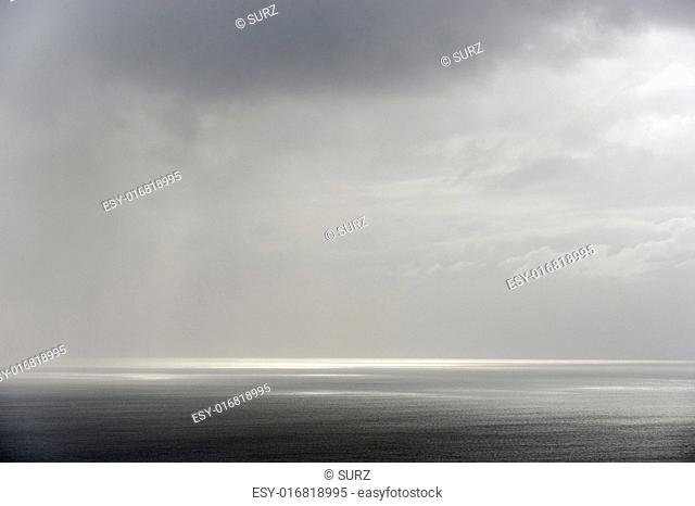 Calm seascape with stormy sky where sun-rays get through the clouds