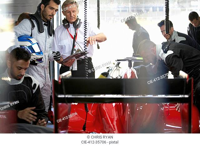 Manager and formula one driver watching pit crew working on race car in repair garage