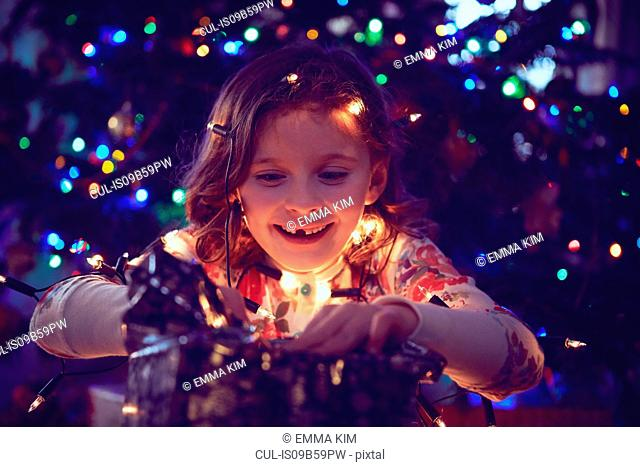 Girl surrounded by lights wrapping christmas presents at christmas