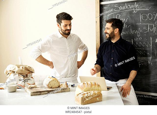 Two bakers standing at a table, using a laptop computer, freshly baked bread, a blackboard on the wall