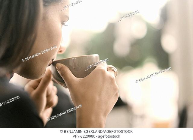 woman sipping coffee at coffee shop, in Munich, Germany