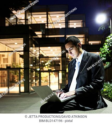 Hispanic businessman using laptop at night in office courtyard