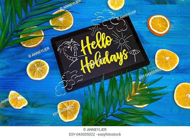hello holidays concept with citrus fruits and palm leaves on blue wooden background