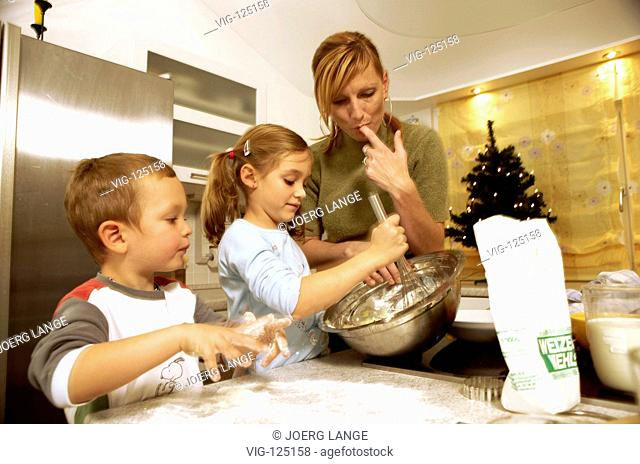 A young mother is baking christmas cookies with her children. - LEIPZIG, GERMANY, 18/10/2005