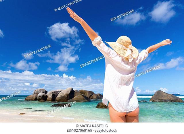 Woman arms rised, wearing white loose tunic over bikini and beach hat, enjoying amazing sea view on Mahe Island, Seychelles