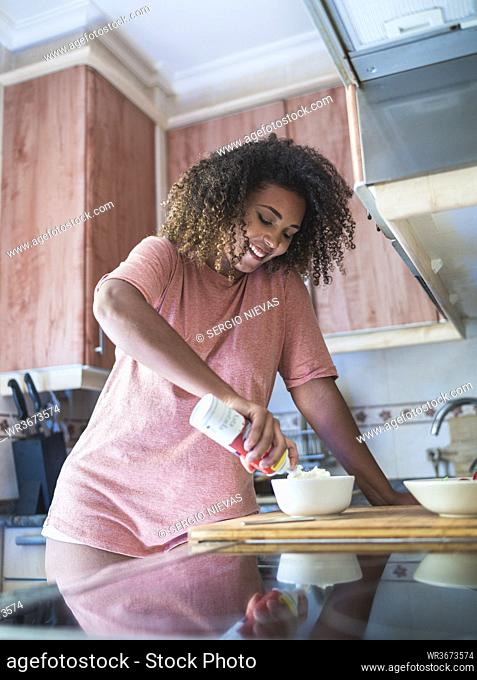 Smiling young woman with curly hair adding whipped cream in bowl at home