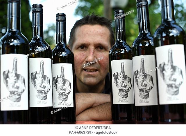 Vintner Fred Strieth from the Thilo Strieth vineyard presents bottles of his Blanc de Noirs 2014, whose label features a raised middle finger and the words...
