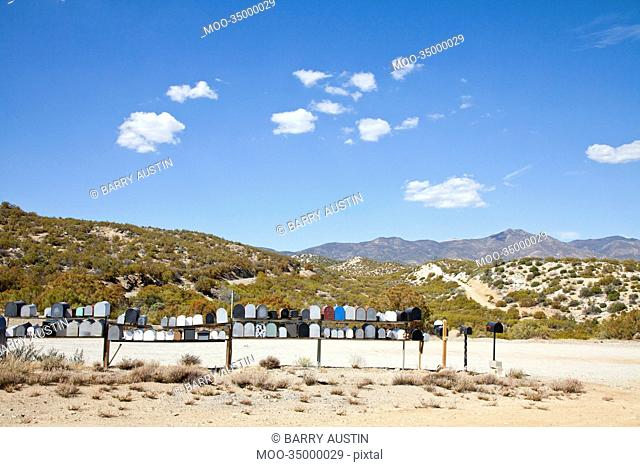 Letter boxes on desert road with mountain background
