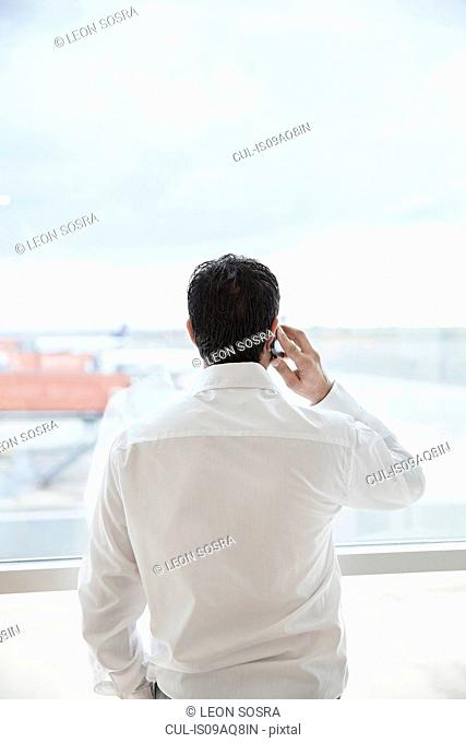 Man at airport window, talking on smartphone