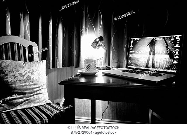 Laptop, lit lamp, coffee mug and chair with pillow