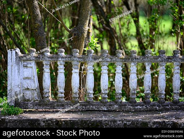fragment of a decorative old fence around a public park, broken parts