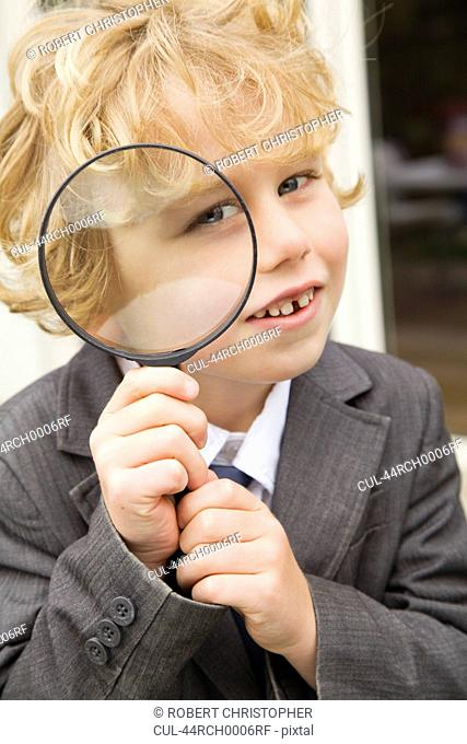 Boy using magnifying glass outdoors