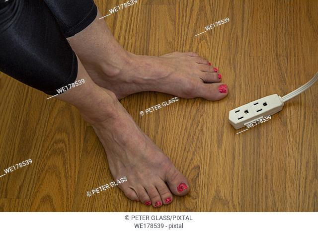 The feet of a young woman, with toenail polish, seen next to an electrical extension cord