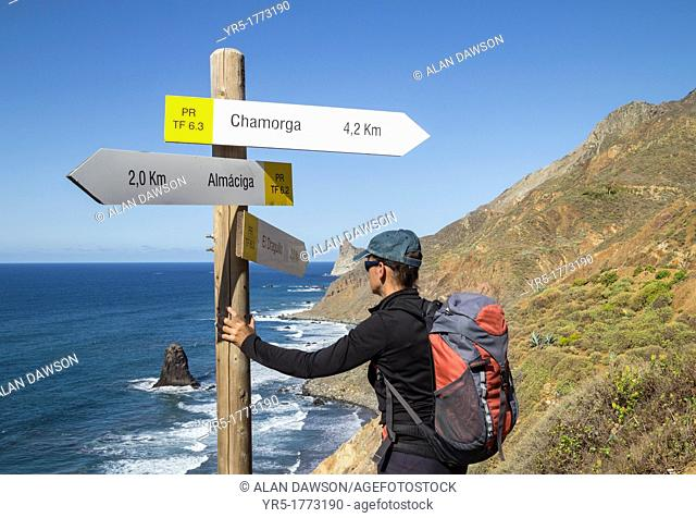 Female hiker near footpath signpost overlooking Roques de Anaga at Benijo in Anaga rural park on Tenerife, Canary Islands, Spain