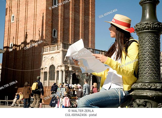 Young woman sitting looking at map in St Marks Square, Venice, Italy