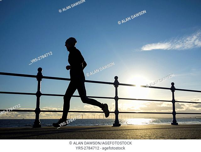 Seaton Carew, north east England, UK. Weather: jogger at sunrise on a bright and cold winter morning at Seaton Carew on the north east coast of England