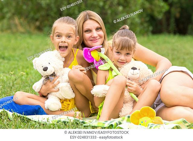 Mother and two daughters sitting with soft toys on a picnic