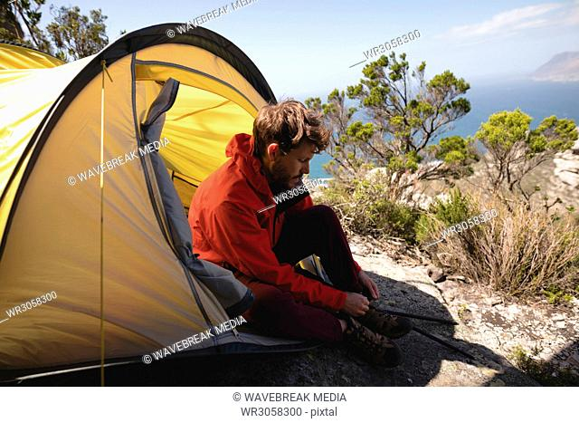 Hiker sitting in tent tying his shoelace