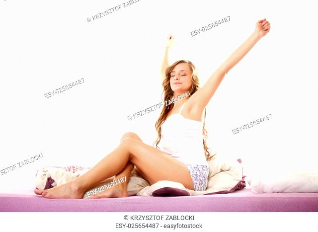 cheerful happy woman waking up with a smile in bed and stretching her arms up