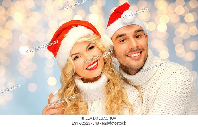people, christmas, holidays and new year concept - happy family couple in sweaters and santa hats over holidays lights background