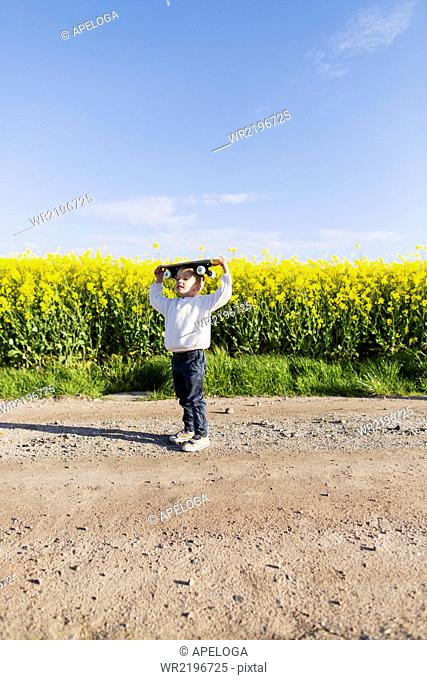 Full length of boy carrying skateboard on head at rapeseed field