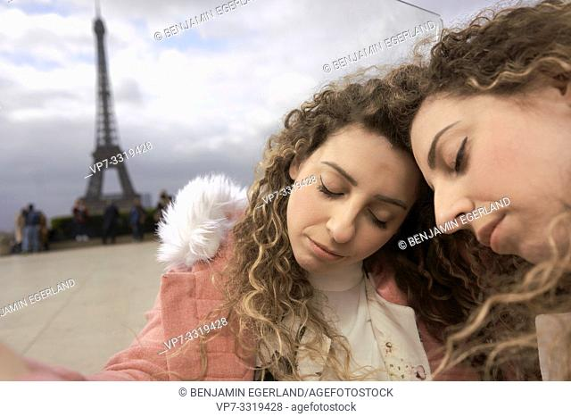 woman leaning against herself in city next to tourist sight Eiffel Tower, at Espl. du Trocadéro, in Paris, France