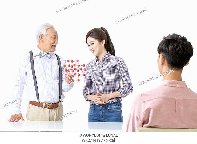 Smiling senior man teaching young people