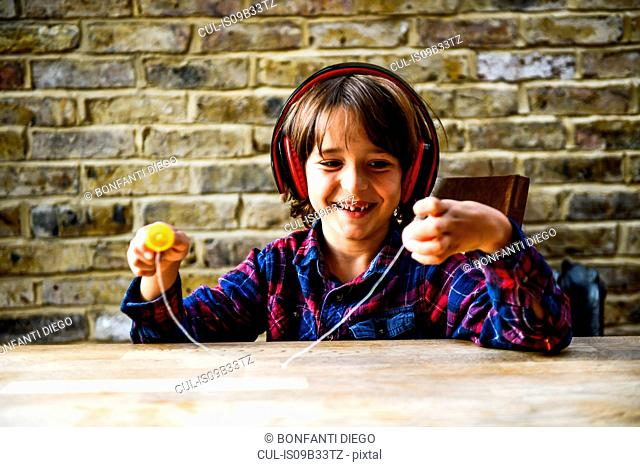 Happy boy sitting at table playing with toy whilst listening to headphones