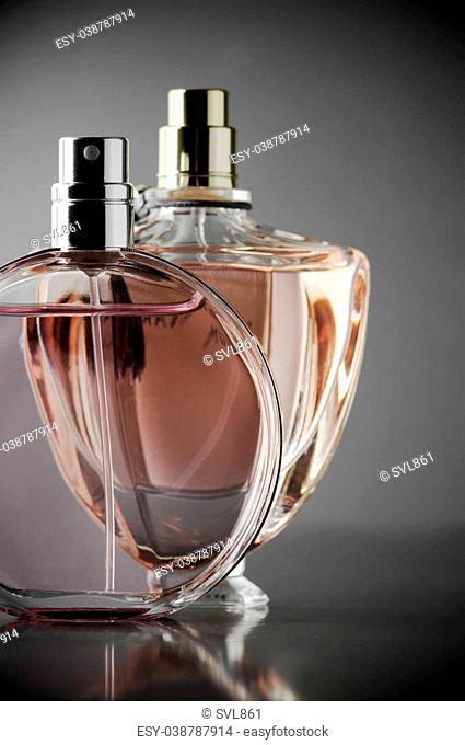Two various bottles of woman perfume on dark gray background. Toned image