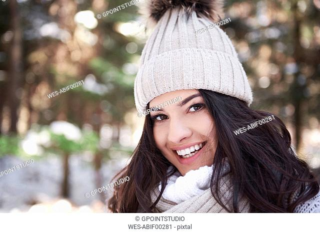 Portrait of smiling young woman wearing woolly cap in forest