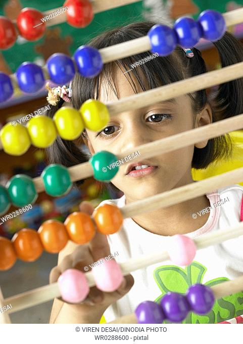 South Asian Indian girl sitting in front of abacus and calculating beads sliding on wires in nursery school MR
