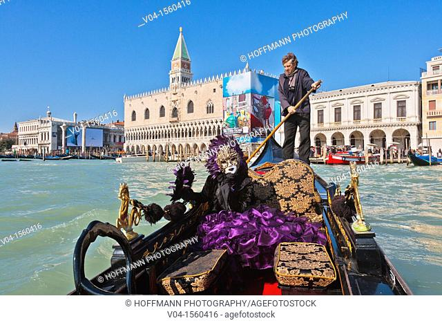 A masked woman in a gondola with the Palazzo Ducale in the background at the carnival in Venice, Italy, Europe