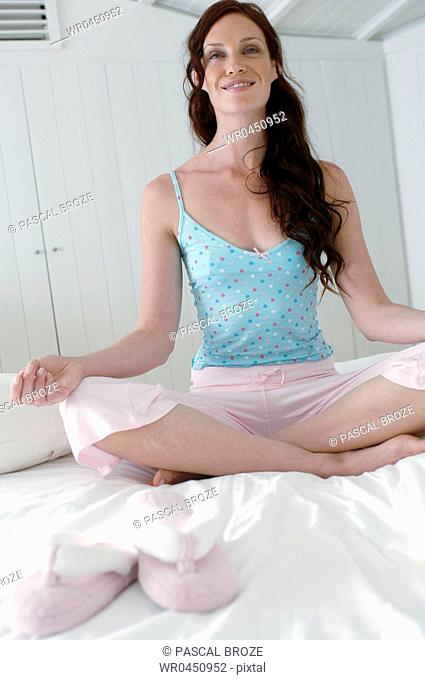 Mid adult woman doing yoga on the bed