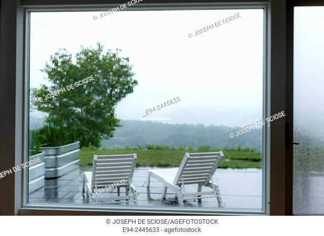Garden furniture as seen through large windows, looking out with raindrops on the glass. Pittsburgh Pennsylvania USA