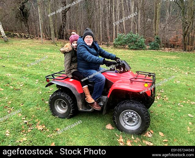 Litle girl is riding on a quad with her father, they are both looking at the camera