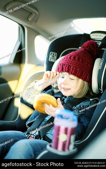 Little happy girl with pink hat enjoys donut in car seat during travel
