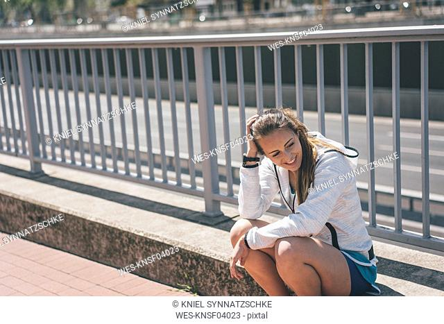 Smiling sportive young woman sitting at motorway