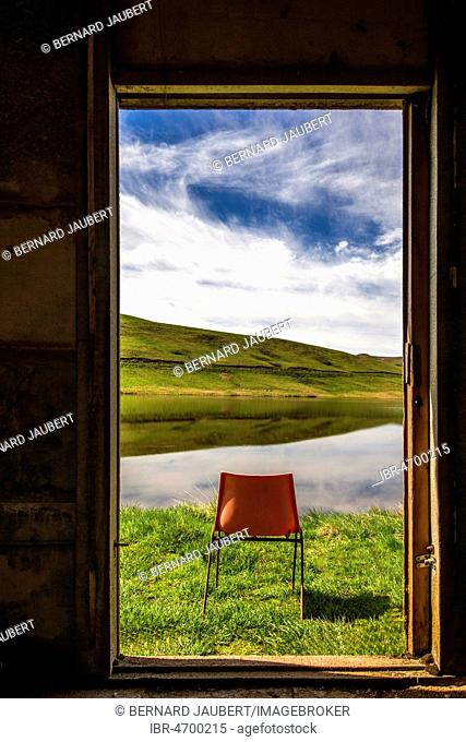 Orange chair standing in front of open window on a lake, Puy de dome department, Auvergne, France