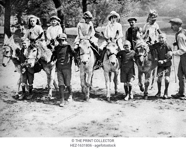 A donkey ride on a bank holiday on Hamstead Heath, London, 1926-1927. From Wonderful London, volume II, edited by Arthur St John Adcock