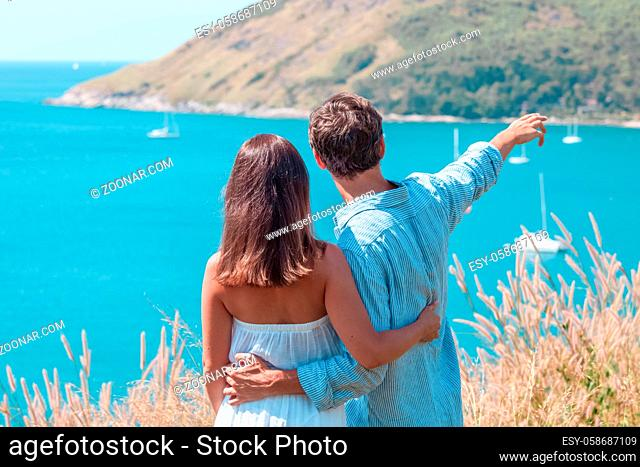 Love, travel, tourism and people concept - couple on vacation standing on mountain, hugging and pointing finger