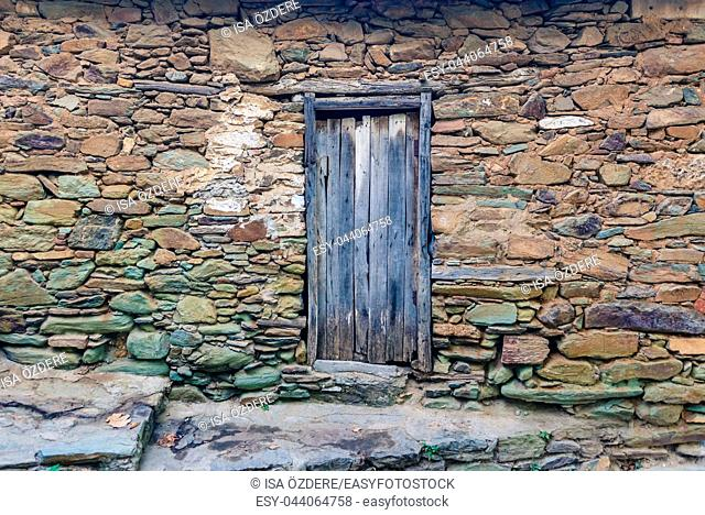 View of old Rustic wooden door and big rocks wall for background. Copy space for editing