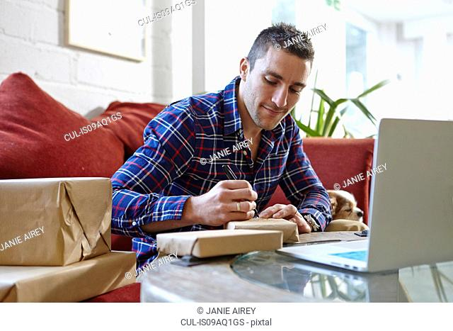 Mid adult man writing address on parcels in picture framers showroom